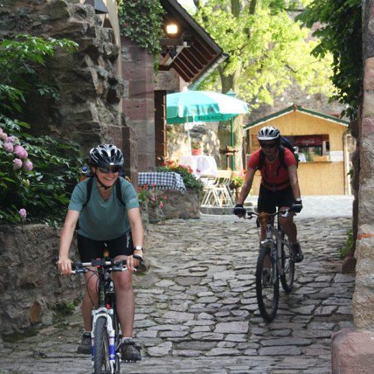 Zwei Radfahrer fahren an einer Burg